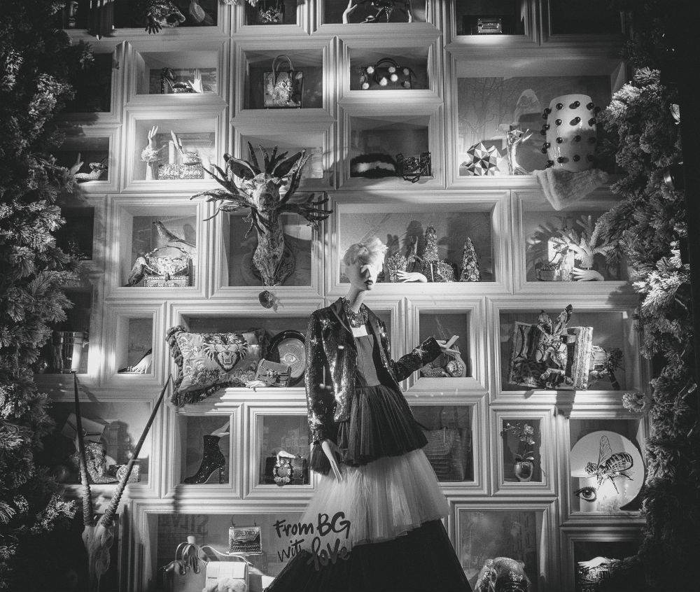 A dressed up female mannequin standing in front of decorated shelves